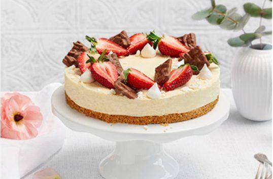 Vit choklad- och färskosttårta garnerad med kex och jordgubbar