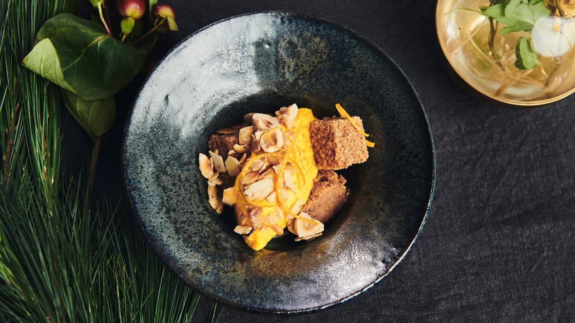 Mjuk pepparkaka med saffransfärskost, doppad i rom och toppad med rostade nötter och apelsin