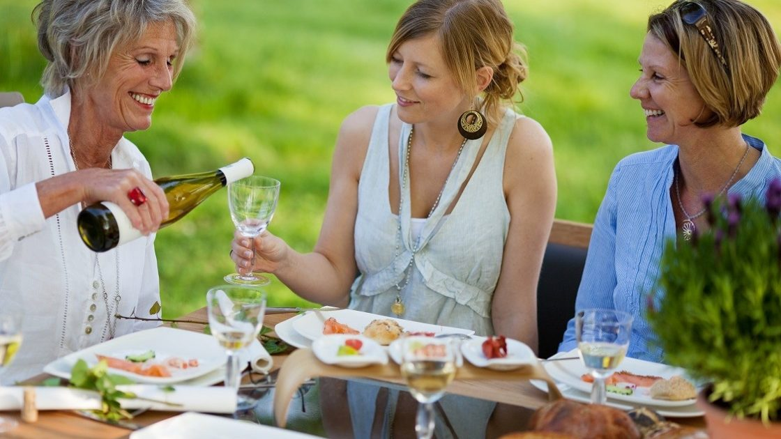 Senior woman pouring wine in glass for daughter at dining table in lawn